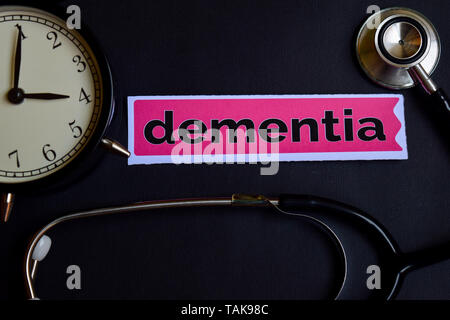 Dementia on the print paper with Healthcare Concept Inspiration. alarm clock, Black stethoscope. - Stock Photo