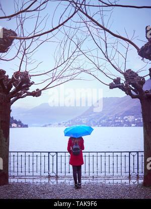 Young woman contemplating Lago di Como in Italy with an umbrella in the rain - Stock Photo