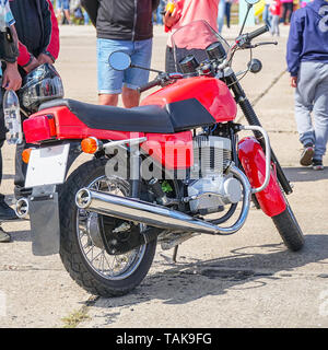 Old red motorcycle on the street. Side view - Stock Photo