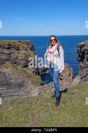 Young woman 25 years old stands at the Irish west coast