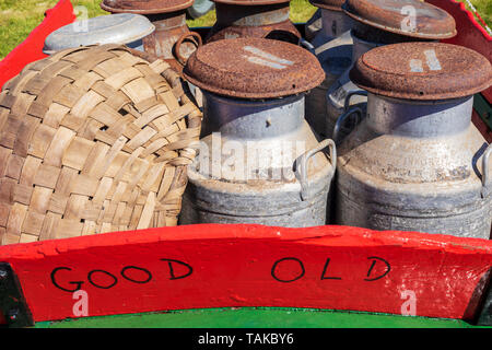 Old rusty traditional styled milk churns and a wicker basket on the back of wooden milk cart, Ayrshire, Scotland - Stock Photo