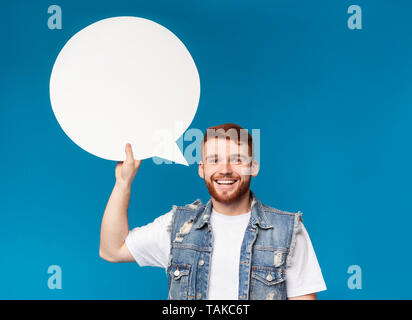 Smiling young man holding blank speech bubble and looking at camera - Stock Photo