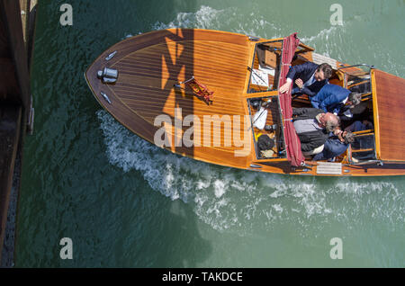 VENICE, ITALY - MAY 20, 2019: Overhead view of the Mayor of Venice - Luigi Brugnaro (sitting top right) travelling with his aids iin his official boat - Stock Photo