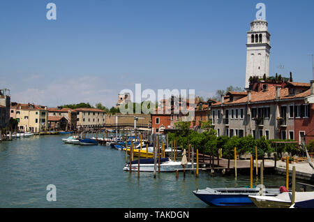 VENICE, ITALY - MAY 10, 2019:  View on a sunny day along the Canale di San Pietro in Venice.  To the right is the bell tower of the Basilica di San Pi - Stock Photo