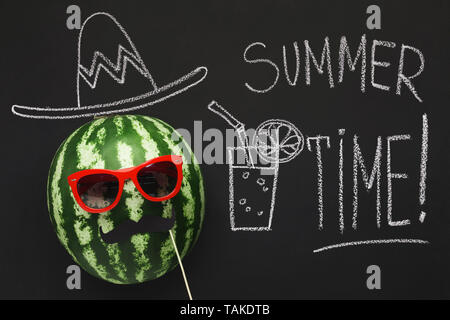 Creative moustached watermelon in sunglasses with drawn cowboy hat - Stock Photo