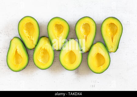 Tabletop view - avocado sliced to halves, arranged in two rows on white working board. - Stock Photo