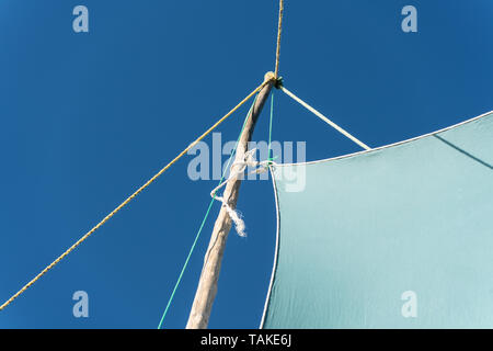 Detail on pirogue - small boat used in Madagascar - mainsail jib blea sky in background - Stock Photo