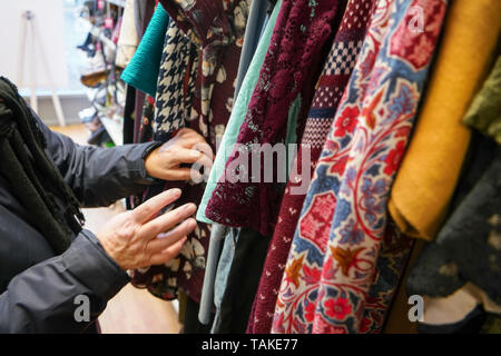 Senior woman going through clothes in second hand thrift charity shop, detail on her moving hands. - Stock Photo