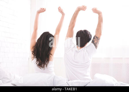 Well rested young couple stretching on bed in morning - Stock Photo