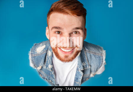 Above portrait of funny millennial redhaired guy, smiling upwards at camera - Stock Photo