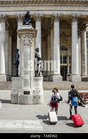 A couple of young tourist ladies with wheelie cases visit The London Troops war Memorial in front of The Royal Exchange Building in London, UK - Stock Photo