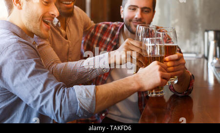 Cheers, Friends. Men Drinking Beer And Clinking Glasses - Stock Photo