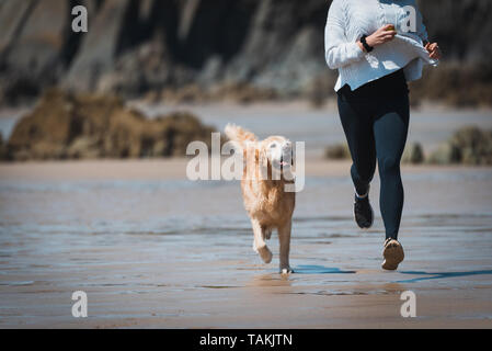 Fit Young woman running with her dog on the beach - Stock Photo