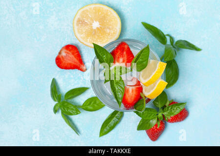 strawberry basil lemonade in a glass, fresh strawberries, basil on a blue background - Stock Photo