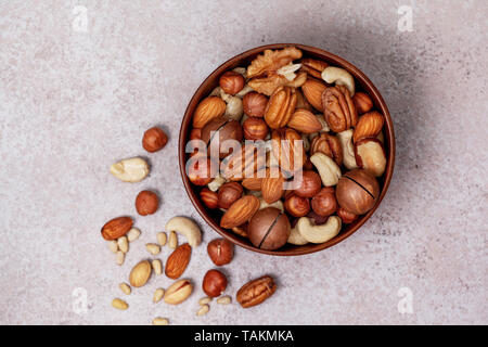 mix of nuts in a wooden bowl on a light background. view from above - Stock Photo