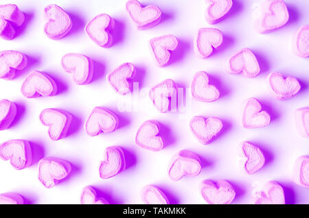 Vibrant and Pastel Purple Heart Shaped Marshmallow Candies Scattered on White Background - Stock Photo