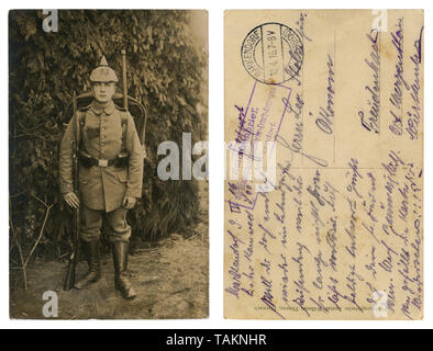 German historical photo: a handsome young soldier in full gear in military uniform with weapons, a rifle with bayonet knife, entrenching shovel, 1916 - Stock Photo