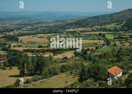 Roof among green trees and farmed fields on hilly landscape near Linhares da Beira. A medieval hamlet with unique architecture in eastern Portugal. - Stock Photo