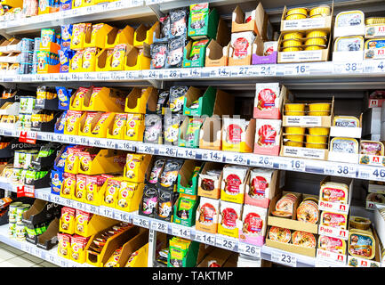 Samara, Russia - May 26, 2019: Various fresh dog food ready for sale on supermarket shelves. Cat food as background - Stock Photo