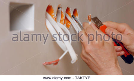 Hands of electrician working with wires close up. Electricians cleans the ends of wires using stationery knife. - Stock Photo
