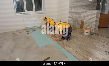 Men in the uniform laying laminate. Builders finishing house renovation. Repair service. - Stock Photo