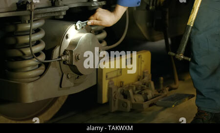 Mechanic repairing train at the depot. Wheel of subway train close up. Technical specialist tightening the screws. - Stock Photo