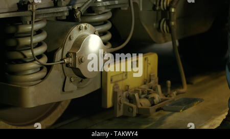 Wheels of the locomotive close up. Engine train wheels and parts close up. Railway transport at service station. - Stock Photo