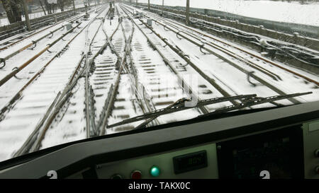 Railway lines in a winter. Snow covered railway tracks, view from drivers cabin. - Stock Photo