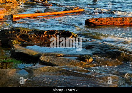 A horizontal image of waves splashing on a rocky shoreline with the beautiful warm light of the early morning on Vancouver Island British Columbia Can - Stock Photo