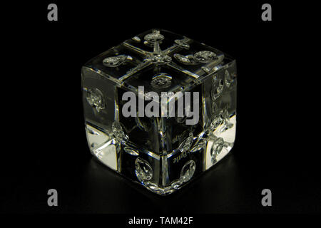 Naples, Italy, 19-April-2019. A gaming dice made of glass on a black background, to accentuate transparency. - Stock Photo