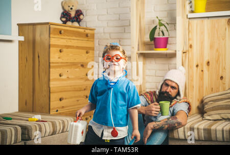 Family time, cheerful boy dressed as doctor in glasses with stethoscope holding first aid kit. Cute child playing with bearded dad, happy childhood - Stock Photo