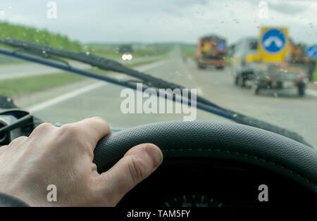 The hand of the driver who moves on a country road in rainy cloudy weather background drops of rain on a windshield and special equipment - Stock Photo