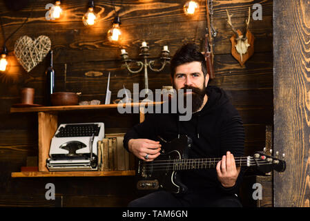 Man bearded musician enjoy evening with bass guitar, wooden background. Soul music. Man with beard holds black electric guitar. Guy in cozy warm - Stock Photo