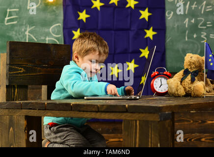 Innovation and technology. Little child use laptop computer in classroom with eu flag, innovation. Innovation in elementary school. Extending your - Stock Photo