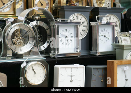 A collection of clocks in store window. Winchester, Hampshire, UK. - Stock Photo