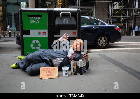 Man laying on sidewalk in front of a garage can wearing a suit and mask impersonating Donald Trump in the Manhattan Financial District - New York City - Stock Photo