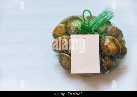 Shellfish enamel venus shell Seafood Clams on net bag in the supermarket - Stock Photo
