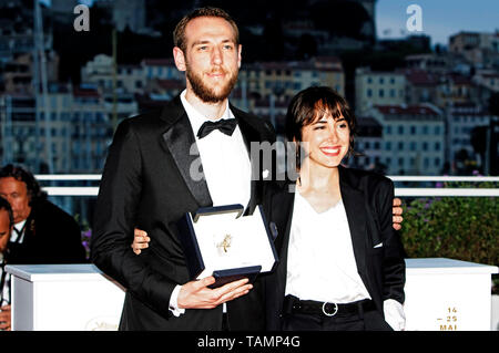 Vasilis Kekatos poses with his Best Short Film Award for the movie 'The Distance Between Us And The Sky' and Agustina San Martin at the award winners photocall during the 72nd Cannes Film Festival at the Palais des Festivals on May 25, 2019 in Cannes, France - Stock Photo