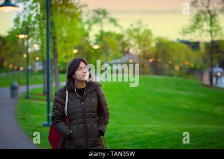 Beautiful young biracial Asian Caucasian woman or teen wearing winter jacket walking along path at lake park near dusk - Stock Photo