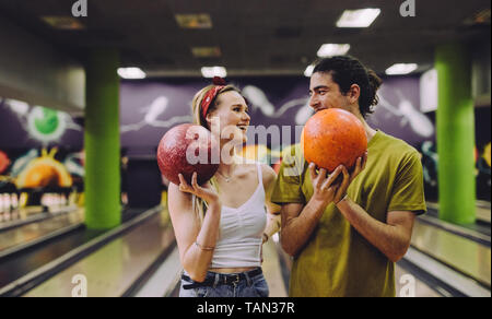 Cheerful young couple at the bowling alley with the balls looking at each other. Young man and woman standing in a bowling club holding balls.