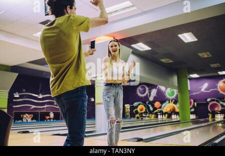 Young man recording woman playing bowling at club. Young friends enjoying playing at bowling arena.
