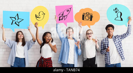 Teenage Friends Holding Social Media Icons, White Wall - Stock Photo