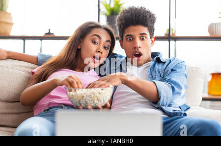 Shocked teen couple watching scary movie on laptop - Stock Photo