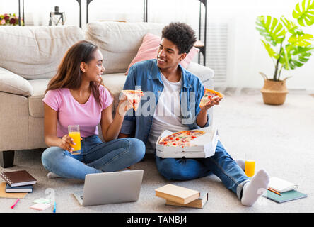 Teen couple eating pizza, sitting on floor at home - Stock Photo
