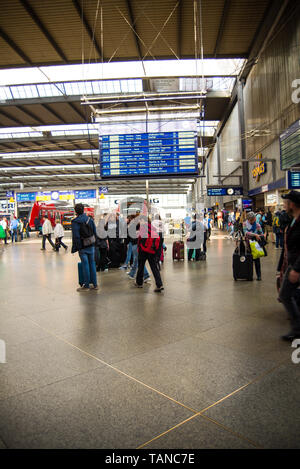 Munich,Germany- May 25,2019: A group of tourists stand in the Hall at Munich Central Station under a sign showing the next departures. - Stock Photo
