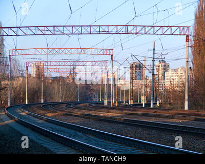The prospect of many multi-lane railways for electric trains with overhead power lines in the early spring morning, high-rise buildings in the backgro - Stock Photo