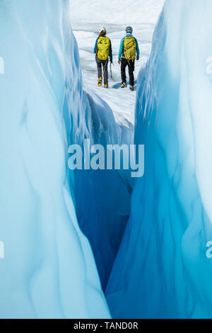 Two ice climbers walking away from a narrow crevasse. The women are ice climbing guides on the Matanuska Glacier in Alaska. - Stock Photo