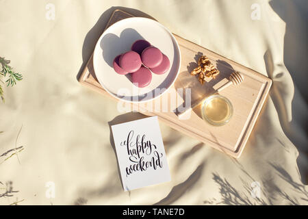 Many colored french macaroons or macaroon on a wooden tray a jar of honey and a round wooden spoon for honey - Stock Photo