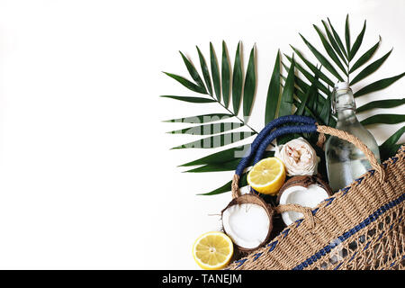 Summer still life composition with straw basket bag, lush palm leaves, lemons, coconut and glass bottle of water isolated on white background - Stock Photo