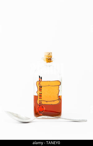 A vintage medicine bottle with cork filled with orange liquid and furnished with an empty label like a parchment roll with red sealing wax and a spoon - Stock Photo